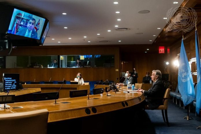 Secretary-General António Guterres (right) listens to Tariq Ahmad, Minister of State for the Commonwealth, the United Nations and South Asia of the United Kingdom (on the screen), at the virtual event